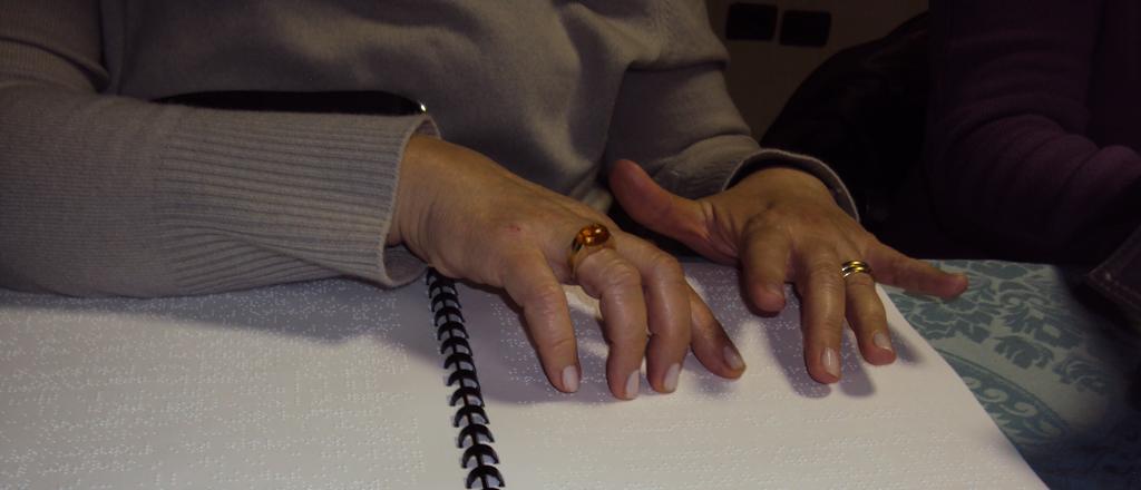 Mani di una donna che legge in Braille