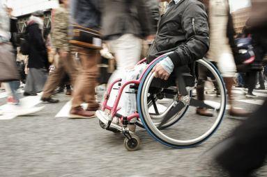 disabile su sedia a rotelle si muove tra la folla in città