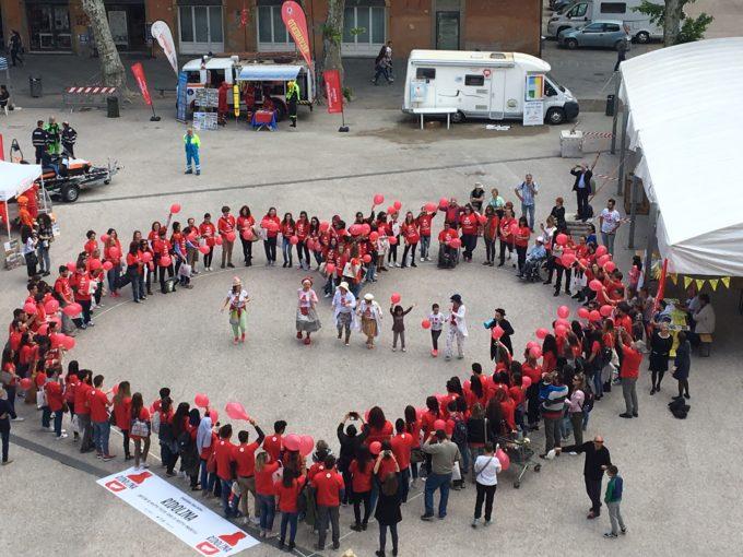 ragazzi che formano una coreografia a forme di cuore durante un evento del festival