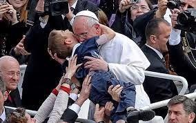 Foto del papa che abbraccia un bimbo dalla papamobile