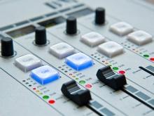 In foto una console di mixer audio utilizzata da persone addette alla regia di un programma radiofonico