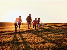 una famiglia che cammina insieme ad un cane in un campo di grano usata come sfondo della locandina dell'evento