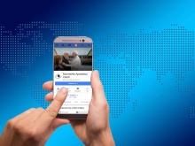 utente che accede su internet alla pagina facebook del mac tramite smartphone