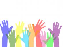 mani colorate rivolte verso l'alto come simbolo del volontariato