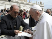 Foto recente di Don Alfonso che porge una copia del suo libro a Papa Francesco