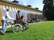 ragazzo con disabilità complessa in compagnia di amici gioca in un parco