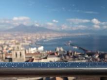 foto dell'opera in braille e panorama di napoli da castel sant'elmo