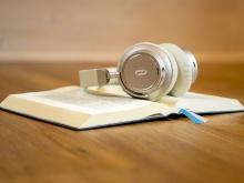 in foto una cuffia appoggiata su un libro aperto