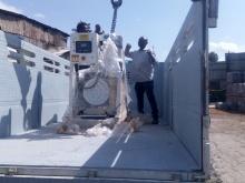 Persona di colore sul camion assiste al caricamento del generatore